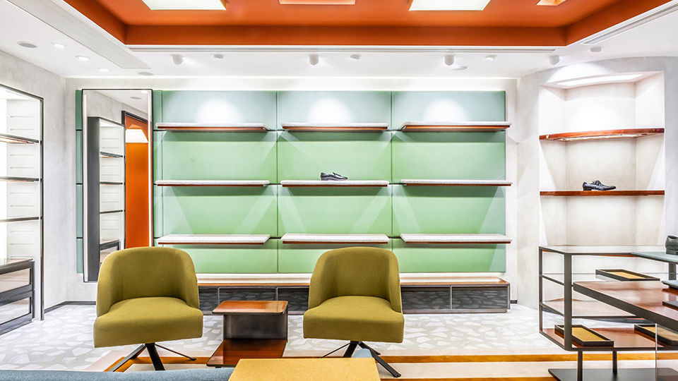 At the back of the store is an area replicating the feeling of a 70's-style library room, dressed with two armchairs and a sofa in the shades of green and blue.