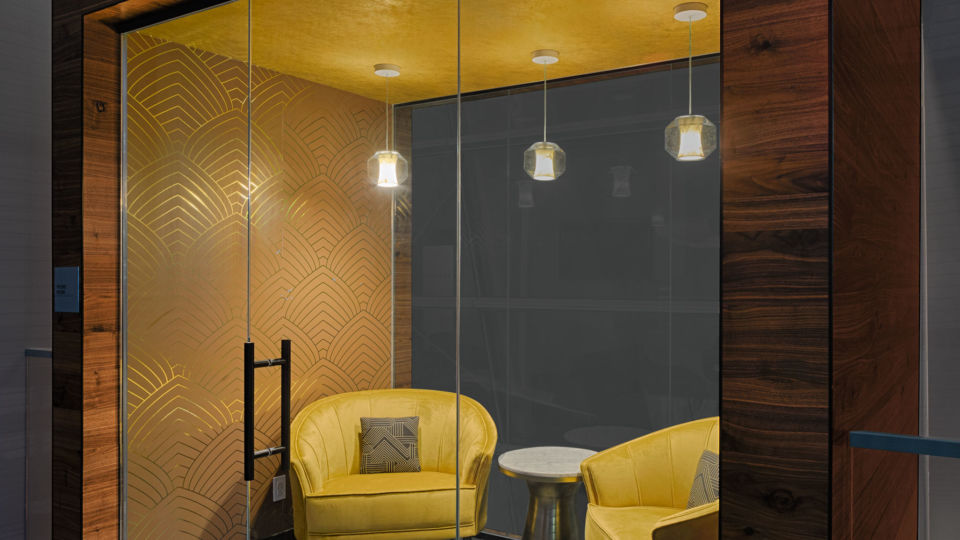 Intimate phone rooms that appear to be floating in the space are located throughout the lounge to offer private escape spaces for travelers. Each room is inspired by a color, a decade and New York architecture.