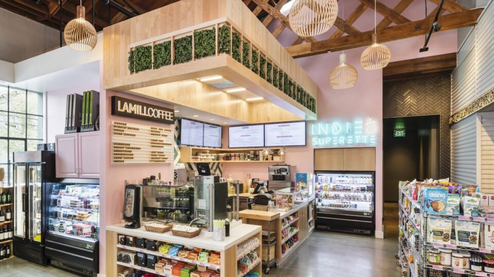 Through the entrance, the open-concept market comes into full view —refrigerators and metal dry storage racks house health-conscious food options.