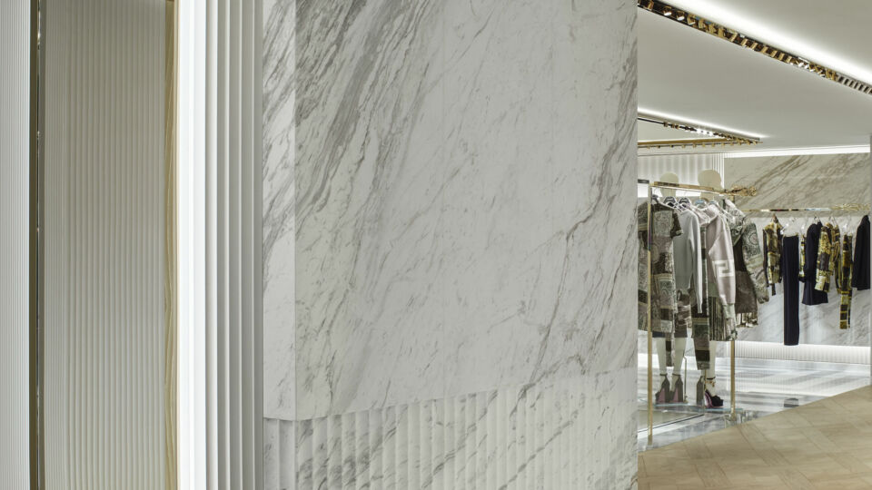 The design features a pristine palette of material: a white and gray selection of marble and the fluted patterned walls are reminiscent of the Gianni Versace residence, reinterpreted in a neutral manner.