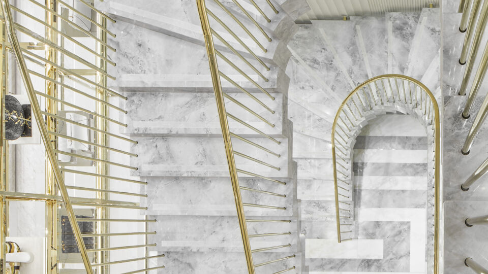 Three floors are connected by sculptural stairs composed of marble and brass.