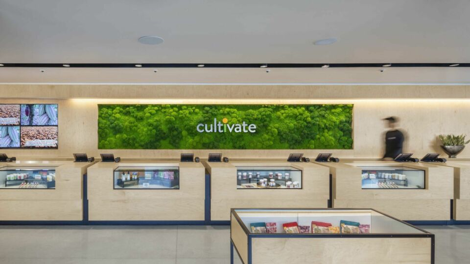 The client services area features natural materials used for the custom wood counters. A preserved moss wall alcove enhances the branded logo.