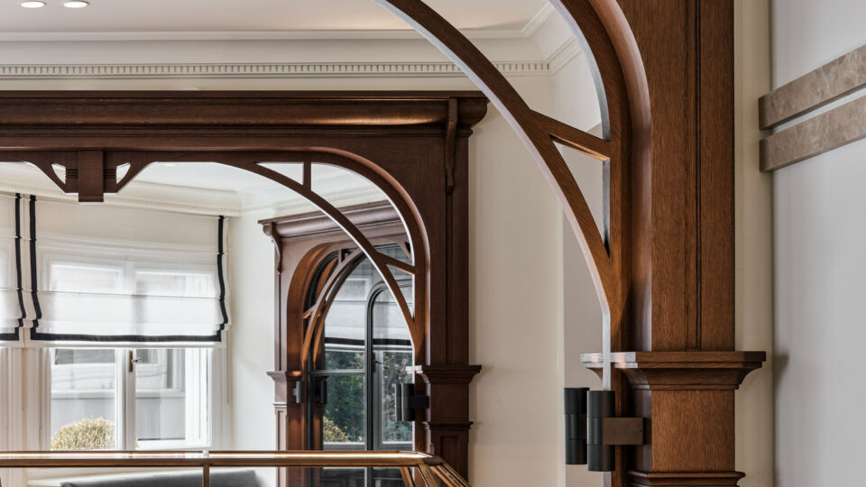 """The arches clearly """"zone"""" different spaces within the showroom. Marquetry flooring with a striking geometric design is used throughout the space, with jewelry showcased in glass display cabinets, anchored by a wooden base with drawers creating accessible storage."""