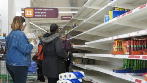 Group of shoppers in store aisle with empty shelves
